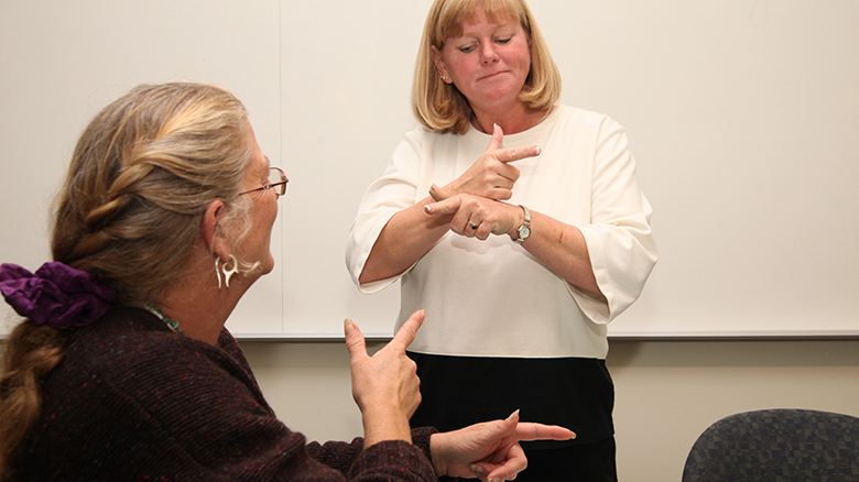 University of Oregon College of Education professor teaching American Sign Language to student