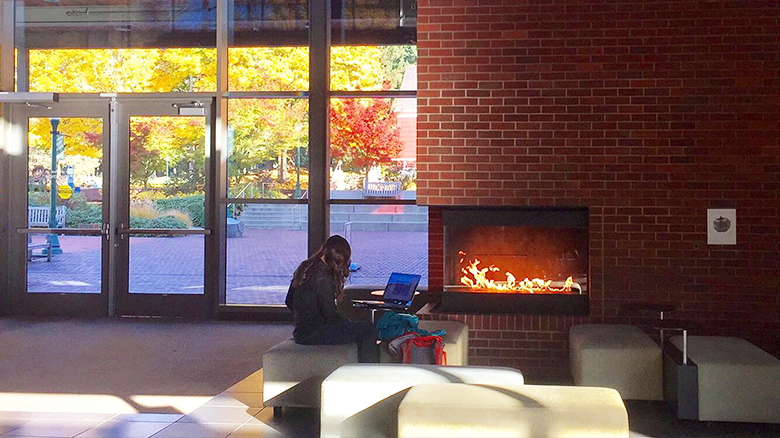 Student studying in the HEDCO lobby in front of fireplace